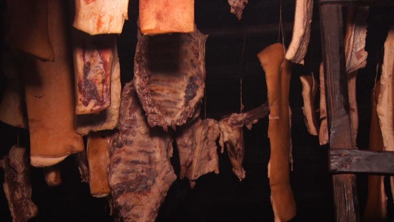 Господар коптить м'ясо за давньою технологією – в окремому будинку-коптильні